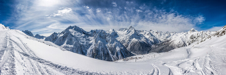 Panoramic view of the ski slope with the mountains Belalakaya, Sofrudzhu, Sulakhat and Semenov-Bashi on the horizon in winter day. Dombai ski resort, Western Caucasus, Karachai-Cherkess, Russia.
