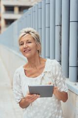 elegante ältere frau ist in der stadt unterwegs und hält ihr tablet in der hand