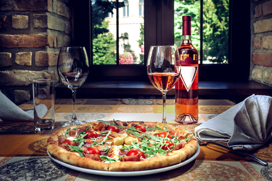 Pizza and red wine on the table.