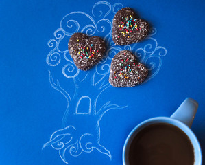 Coffee art. Picture of a picture of a tree invented and painted with his own hands decorated with biscuits with a cup of coffee. Composition with morning coffee, breakfast