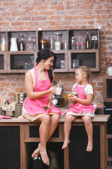 Cheerful family having fun in the kitchen. Young mother and her little daughter baking together