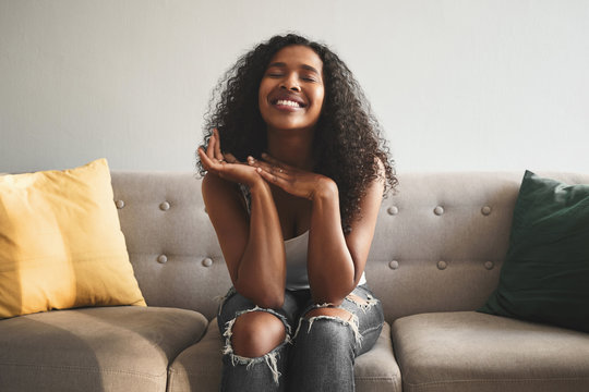 Positive human facial expressions, emotions, feelings and reaction. Indoor shot of emotional happy young mixed race woman wearing ripped jeans, closing eyes and smiling broadly, expressing joy