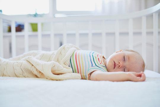 Baby girl sleeping in co-sleeper crib