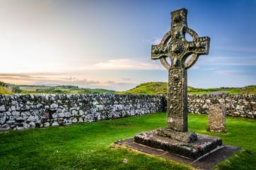 Stone religious celtic Kildalton cross on a cemetary beside a church on Islay island during sunset, Hebrides, West Scotland