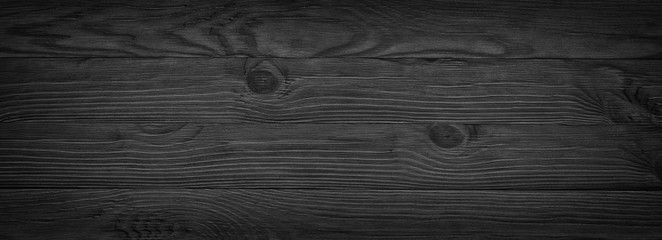 Panorama of black wooden boards, gloomy wood texture, dark background