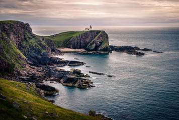 Coastline and a lighthouse on a cliff close to the Man of Storr in the sea - North-West Scotland