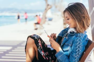 junge frau sitzt am meer und hört musik mit ihrem handy