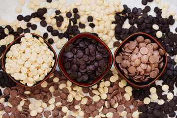 An assortment of fine white, dark, and milk chocolate in bowls overhead