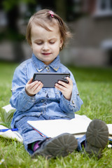 Little beautiful child girl using smartphone as symbol of work or study. Connect to the Internet with smartphone.