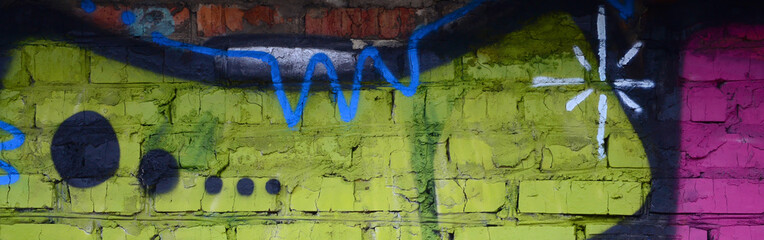 Fragment of graffiti drawings. The old wall decorated with paint stains in the style of street art...