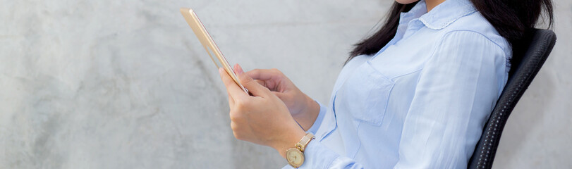Closeup banner website young asian woman touching tablet computer sitting on concrete cement background, freelancer female calling telephone, communication concept.