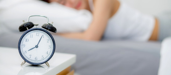 closeup banner website alarm clock and beautiful asian young woman in morning, wake up for sleep with alarm clock, relax and lifestyle concept.