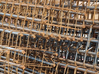 Stacks of Fabricated Rebar cages that will be used in cement forms stand ready.