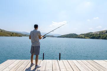 Printed kitchen splashbacks Fishing Back view man fishing on the lake, on sunny day
