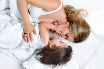 Daughter hugging mother in the bed