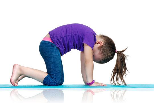 Little girl practicing cat yoga pose