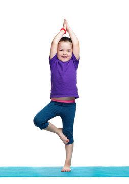 Little girl standing in tree yoga pose