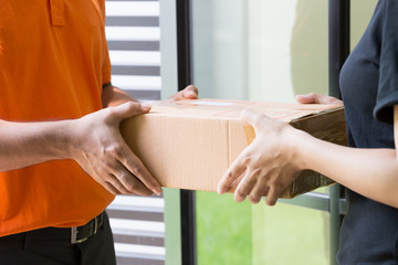 Woman customer accept and receive parcel from delivery man at front home
