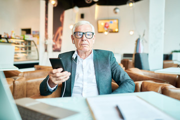 Portrait o modern senior businessman relaxing at table in cafe and listening to music from smartphone, copy space