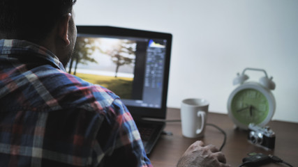 Back view of male photographer working at home on laptop, retouching photos