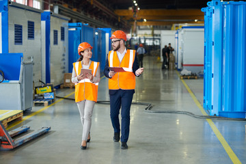 Full length  portrait of bearded businessman wearing hardhat talking to smiling  female factory worker while discussing production in workshop, copy space Wall mural