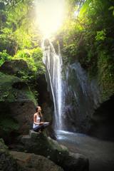 Serenity and yoga practicing at waterfall