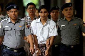Detained Reuters journalists Kyaw Soe Oo and Wa Lone are escorted by police as they arrive before a court hearing in Yangon