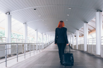 Back of businesswoman taking a luggage and walking towards the platform way - business travel and commuting people concept.