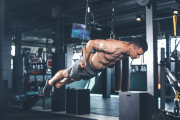Shredded guy is feeling tension while exercising with gymnastic equipment. He is straightening all body and bringing it to parallel to floor. Male is holding handles and looking down