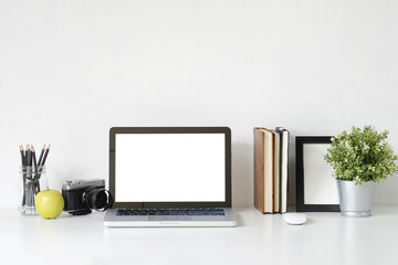Stylish table Mockup laptop computer, camera, book and photo frame on white desk with office supplies.