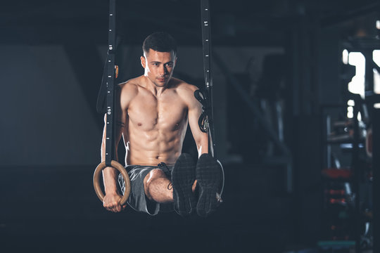 Determined guy is exercising with gymnastic outfit in gym. He is pulling up and bringing legs to parallel to the ground. Male is balancing while straining all body