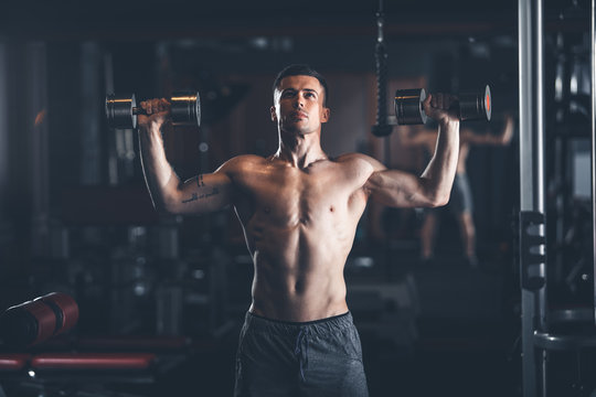 Shapely topless guy is standing and lifting dumbbells in gym. He is pressing equipment up with effort. Strong male training concept
