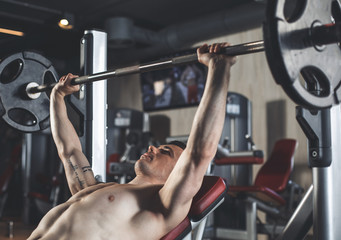 Strained athlete is doing chest press-ups with weight. He is using equipment for strength training. Male is lying on machine bench during lifting