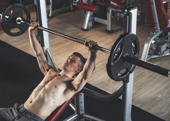 Top view of shapely topless man exercising with sport machines. He is lying on bench and lifting heavy barbell. Sportsman is working on chest muscles