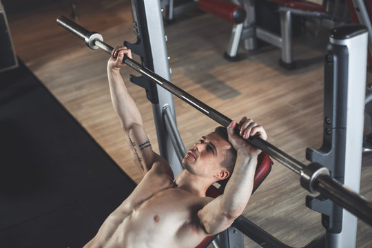 Top view of bodybuilder doing chest press with barbell. He is using machine by lying on bench and fixing equipment on it. Man is training strength and relief