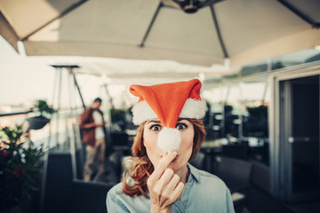 Look at me. Joyful pretty woman in red Santa Claus hat having fun at New Year party. Male friend and cozy cafe on blurred background