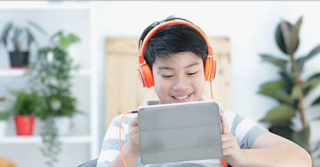 Asian teens playing tablet computer with smile face .