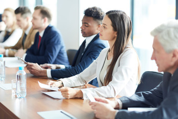 Young serious businesswoman, one of participants of summit, and her colleagues listening attentively to report of speaker