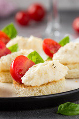 Canape with cheese mousse, cherry tomato and basil, small sandwich on crispy toast with cheese and garlic dumplings. Delicious appetizer, wine snack