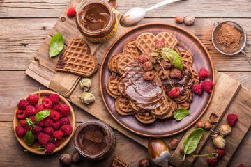 Freshly made belgian waffles with chocolate hazelnut paste and raspberry. top view