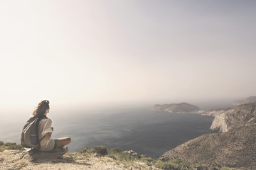 traveling woman relaxes and meditates on the peak of a mountain