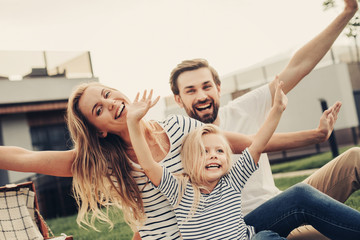 Portrait of beaming woman and cheerful male situating near satisfied child while gesticulating hands. Glad couple with daughter resting outside concept