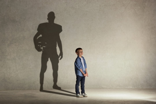 American Football champion. Childhood and dream concept. Conceptual image with boy and shadow of fit athlete on the studio wall