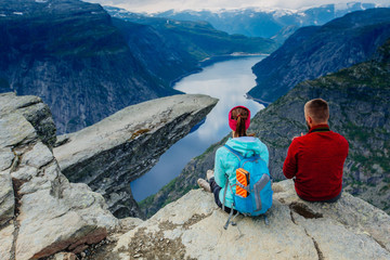 Back of couple sitting against amazing nature view over view on Trolltunga. Location: Scandinavian Mountains, Norway, Stavanger. Artistic picture. The feeling of complete freedom