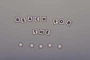 Retro image of a saying Reach for the stars assembled by paper cut letters and stars over grey background.