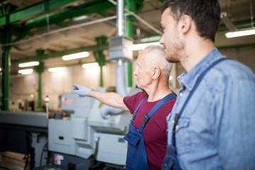 Mature foreman showing workplace to his colleague in factory