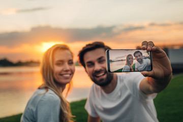 Portrait of positive bearded male and smiling girl watching at phone while doing selfie outdoor. Happy couple experiencing nature concept