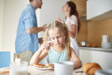 Upset and stressed little girl trying to eat while sitting by breakfast and her parents having argument on background