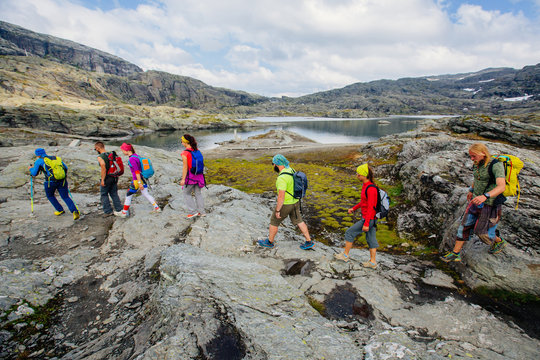 Group of seven hikers men and woman walking with backpacks and trekking poles along water lake in mountain valley during Norway travel.