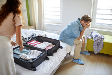 Young wife getting up with suitcase while her face palm husband sitting on bed near by